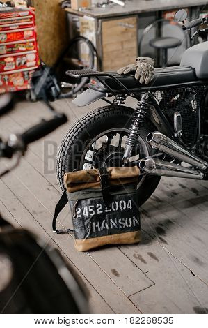 Leather backpack near the motorcycle. Half black motorcycle in the garage. Motorcycle kaferacers. Exclusive leather backpack. Backpack handcrafted. stock photo
