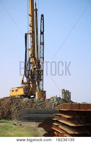 yellow drill rig on a construction site stock photo