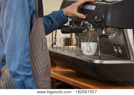 Professional coffee machine. Closeup of professional bartender in denim shirt and apron making coffee drink. stock photo