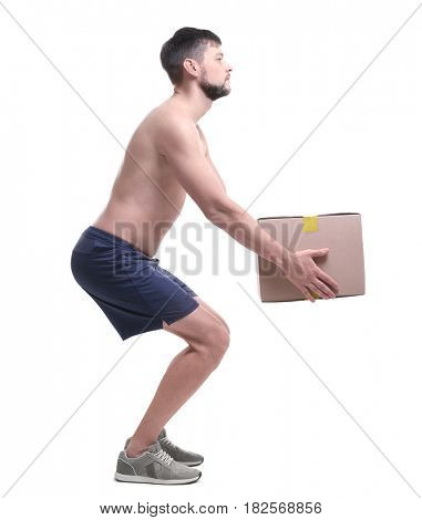 Posture concept. Man lifting heavy cardboard box against white background stock photo