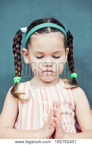 Little girl is praying. Mix asin kid stock photo
