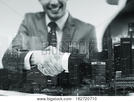 business, cooperation, partnership and people concept - two businessmen shaking hands at office over
