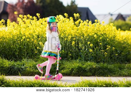Child riding scooter on way back to school. Little girl playing outdoors learning to balance on kick board. Kids ride scooters in suburbs street. Preschooler in safe helmet on bike or roller. stock photo