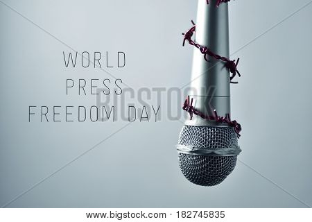 closeup of a microphone encircled by a red barbed wire and the text world press freedom day on a gradient gray background stock photo