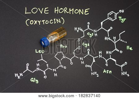 Close-up blue cap sample vial on paper with chemical formula of Oxytocin (love hormone) stock photo