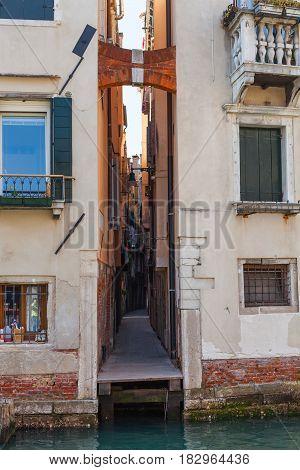 travel to Italy - narrow street Calle del Magazen from waterfront of Rio de la Pieta canal in Venice city in spring stock photo