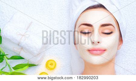 Spa Woman applying Facial clay Mask. Beauty Treatments. Close-up portrait of beautiful girl with a t