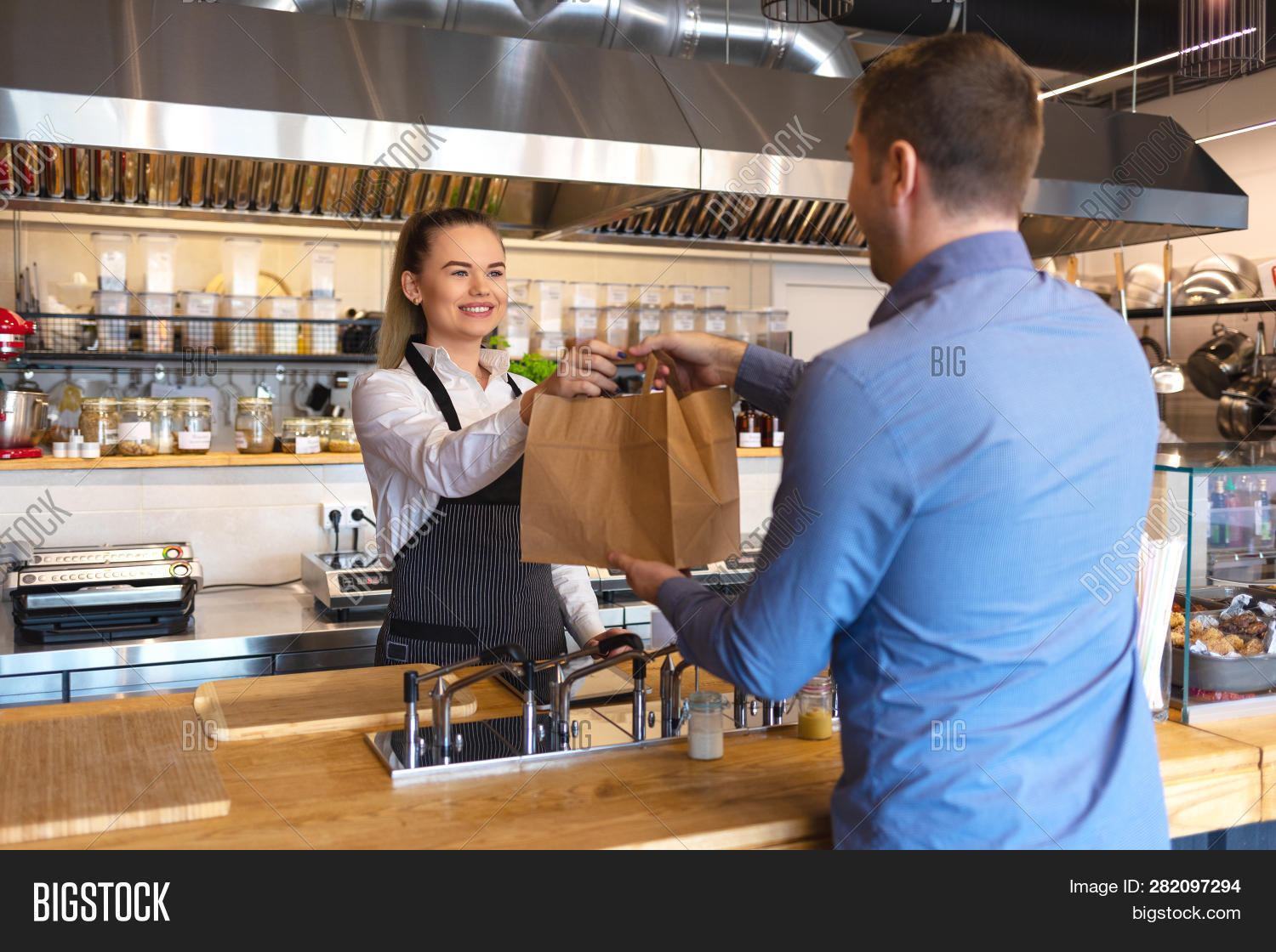 Smiling Young Waiter Giving Food Order To Man Client At Small Fast Food. Happy Woman Standing Behind
