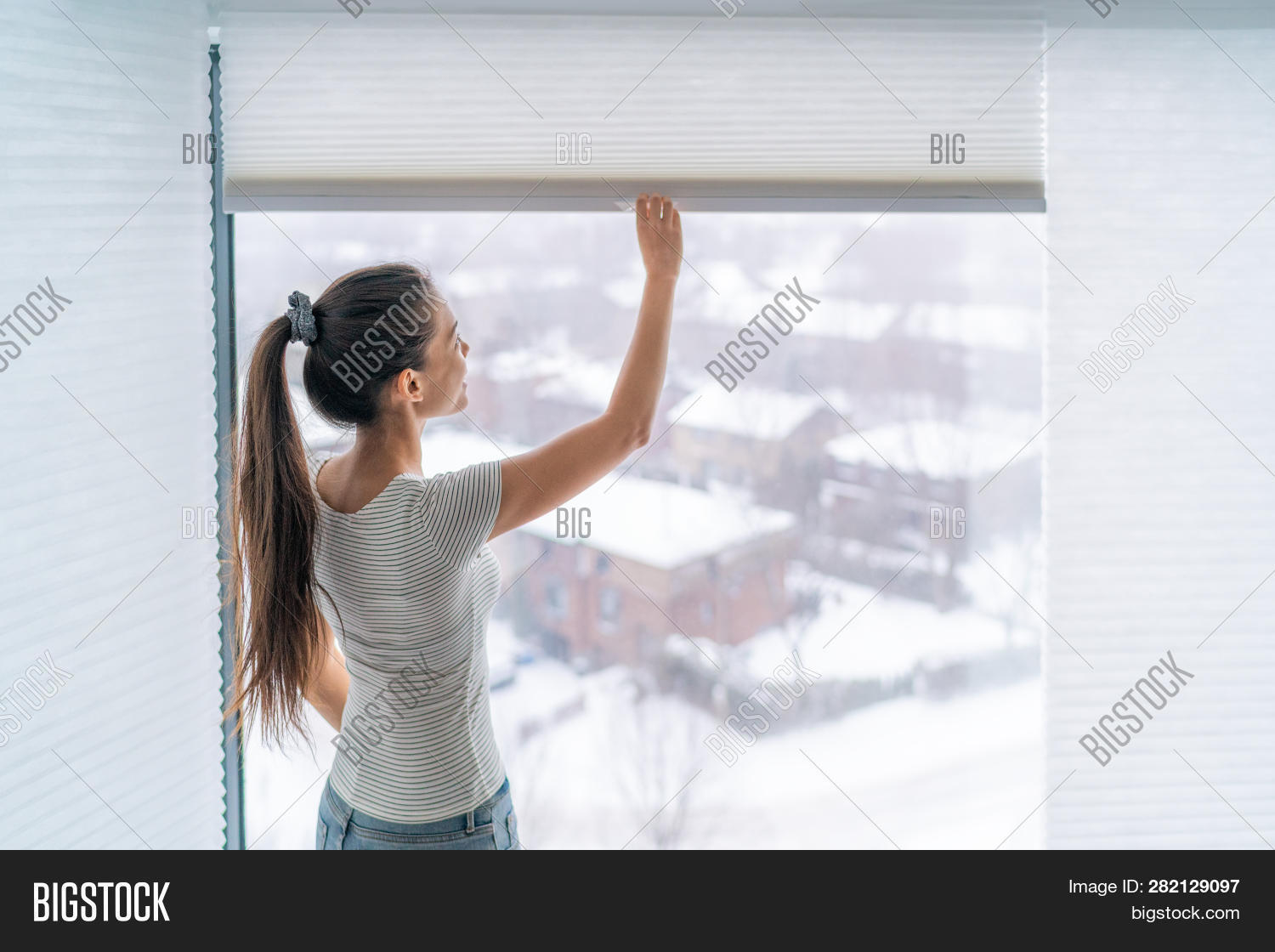 Home blinds window shades woman opening shade blind during winter morning. Asian girl holding modern cordless top down luxury curtains indoors.