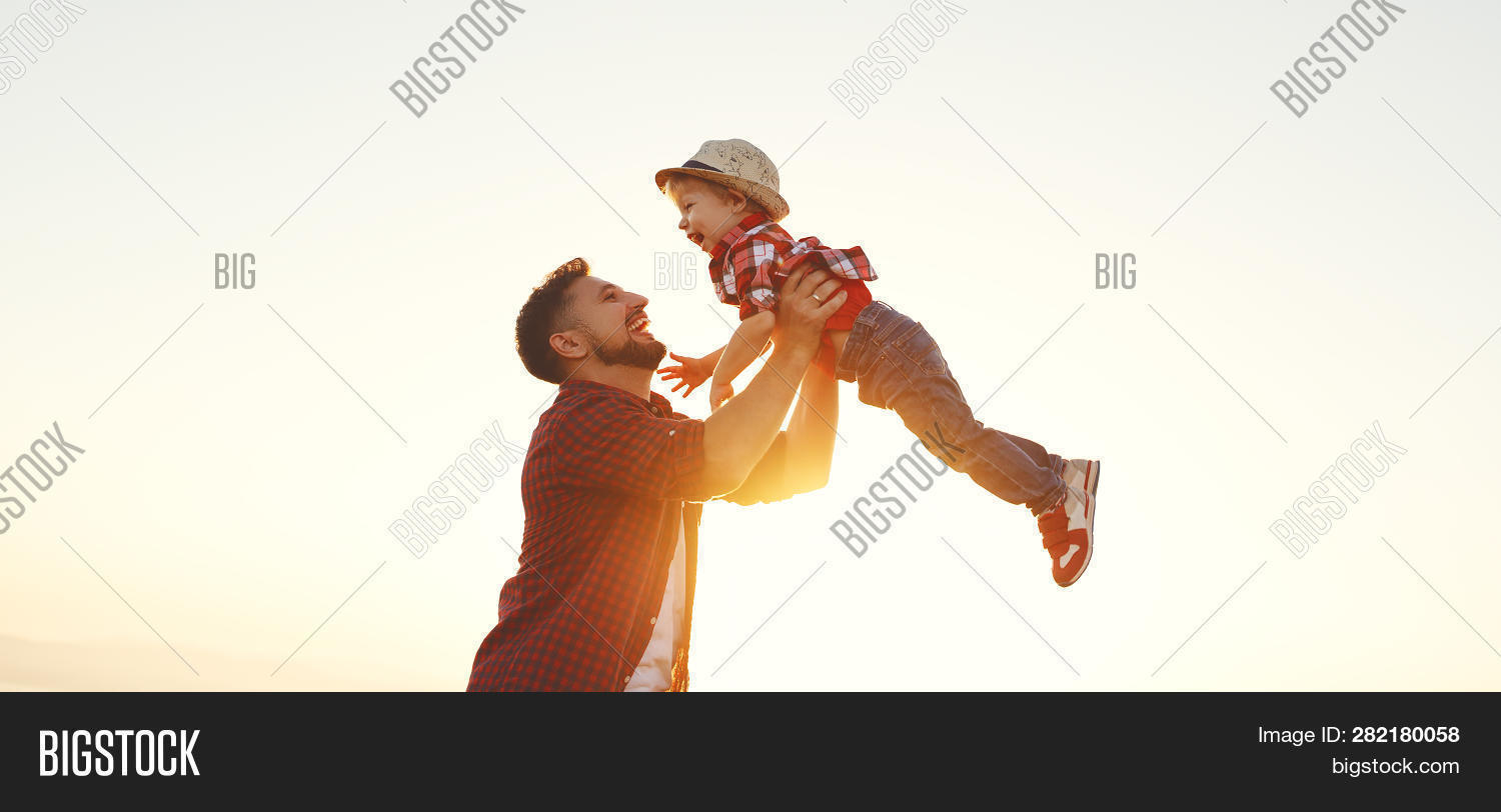 Father's Day. Happy Family Father And Toddler Son Playing And Laughing On Nature At Sunset.