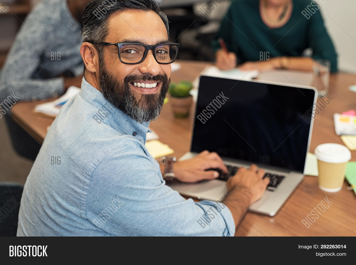 Mature middle eastern businessman using laptop at desk in busy office.Happy smiling casual man looki