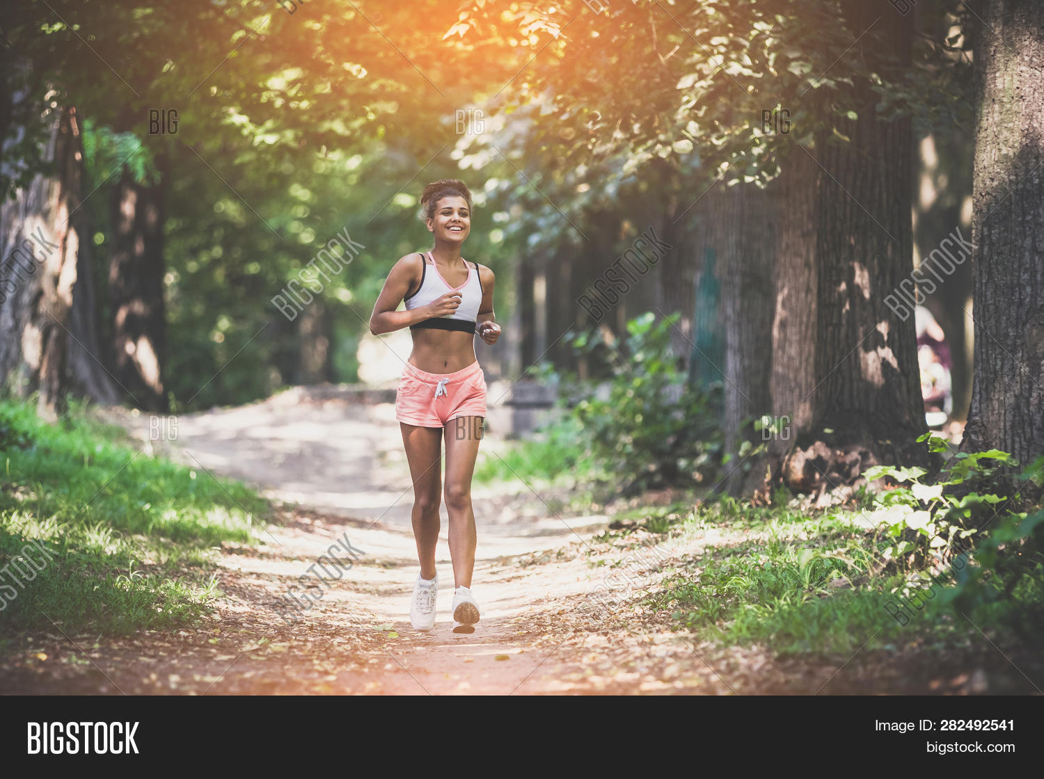 Young lady running. Woman runner running through the summer park road. Workout in a Park. Beautiful fit Girl. Fitness model outdoors. Weight Loss