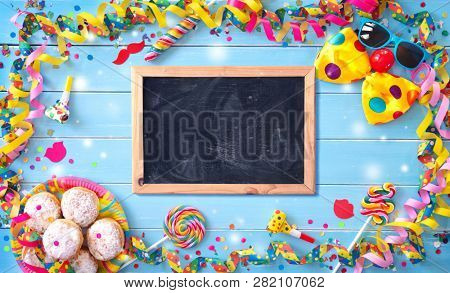 Krapfen, berliner or donuts with streamers, confetti and other party accessoires on blue wooden planks. Colorful carnival or birthday background stock photo