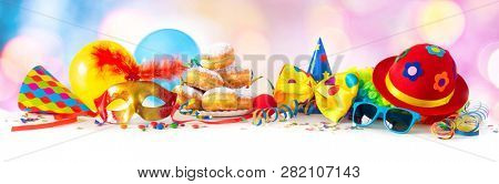 Colorful carnival or party background with donuts, balloons, streamers and confetti and funny face formed from wig, hat and eyeglasses  stock photo