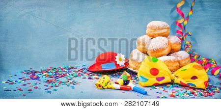 Krapfen, berliner or donuts with bow tie, party hat, streamers and confetti. Colorful carnival or birthday background stock photo