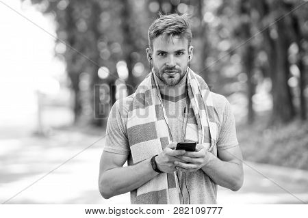 Checking all training updates. Man athlete setting up fitness tracker with smartphone app, nature background. Sportsman training with pedometer gadget. Athlete with fitness tracker or pedometer. stock photo