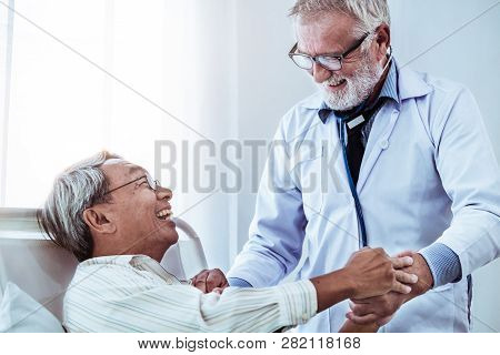 Mature doctor talking and examining health of senior patient in hospital ward. Medical healthcare and doctor staff service concept. stock photo