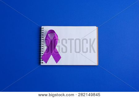 Purple ribbons and open notebook on blue background, Alzheimer disease, Pancreatic cancer, Epilepsy awareness, domestic violence awareness,fibromyalgia awareness, world cancer day. copy space stock photo
