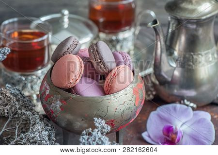 Freshly baked macaroons on metal plate with small white flowers and tea appliances composition on wooden background. stock photo