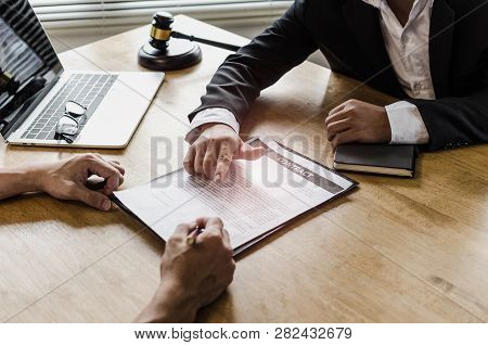 client customer signing contract and discussing business with legal consultants, notary or justice lawyer with laptop computer and wooden judge gavel on desk in courtroom office, legal service concept stock photo