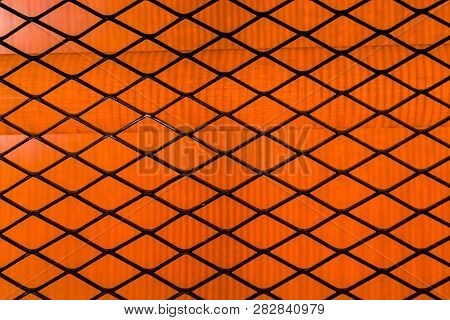A black checkered lattice on an orange bright background. stock photo