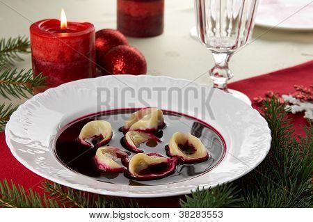 Red borscht (Czerwony barsz) with mushroom dumplings. Traditional polish Christmas Eve dinner / supper. stock photo