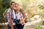 glad youthful couple trekking in mountain