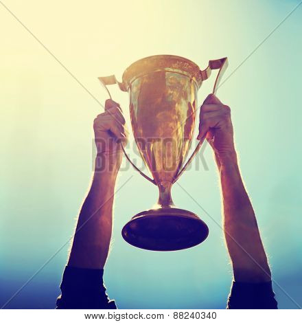 a man holding up a gold trophy cup as a winner in a competition toned with a retro vintage instagram