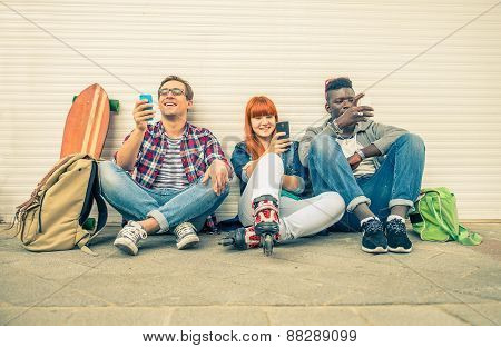 Group of friends of different ethnics sitting on the street and looking at mobile phone - Young modern hipster people having fun with new technologies - Multiracial group representing the addiction to technology stock photo