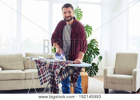 Wide shot of awesome bachelor ironing attentively shirt on ironing board stock photo