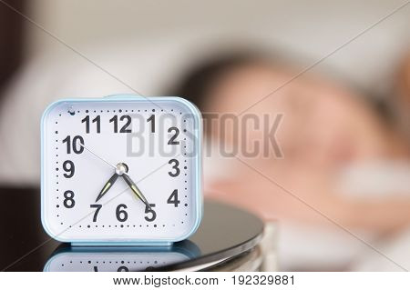 Close up image of modern alarm clock on bedside table with blurred person sleeping in bed in background. Wake up in early morning, stable sleep routine, healthy sleep schedule, wake-up time concept