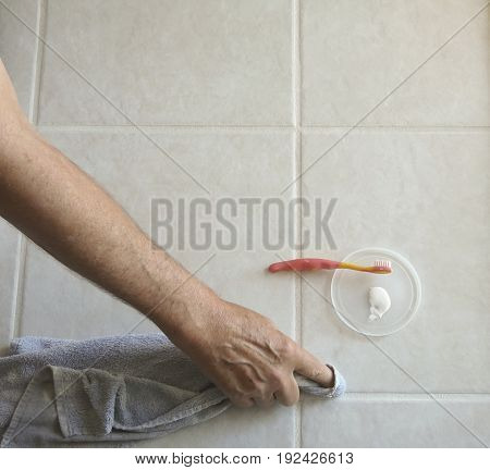 Male homeowner uses toothbrush and grout color/sealer to paint tile grout lines in the kitchen of his residence to repel oils and prevent stains. stock photo