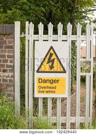 an electric safety sign outside on metal gate with electric bolt in triangle yellow and black danger live wires overhead england uk restriction power grid