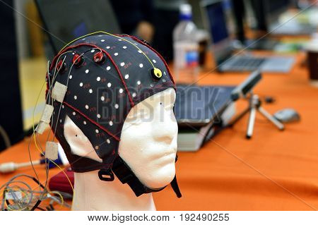 The electroencephalogram (EEG) head cap with flat metal discs (electrodes) attached to a white plastic model's head shown in a science exhibition with laptops blurred at the background. EEG is widely used in brain science research and clinical application stock photo