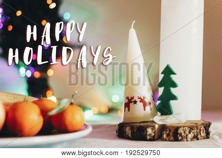 happy holidays text sign on christmas rustic table with candle with reindeers and felt tree and fruits on colorful lights background. space for text. seasonal greetings holidays card concept stock photo