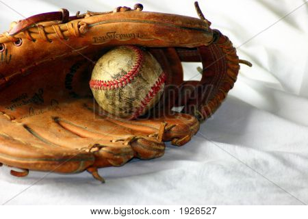 Old beat-up baseball in a glove white background stock photo
