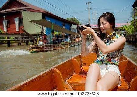 Damnoen Saduak floating market tourist. Young traveler woman holding camera sitting in canal ferry Beautiful happy smiling mixed race asian chinese woman. Asia holiday and travel vacation concept stock photo