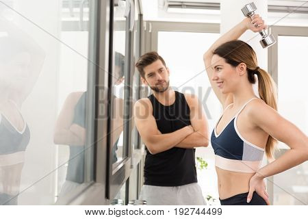 Slim girl excersising on a gym with her coach stock photo