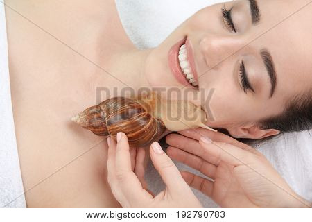 Young woman undergoing treatment with giant Achatina snail in beauty salon, closeup stock photo