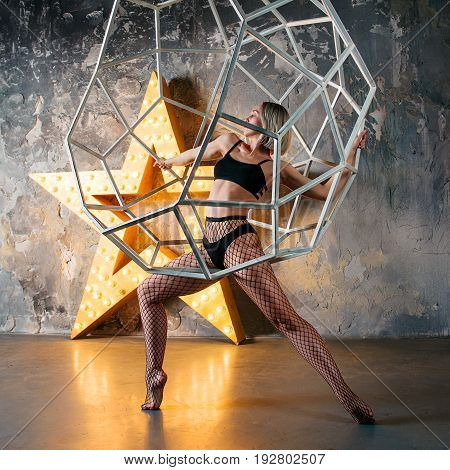 portrait of beautiful attractive blonde woman dancer with huge star on the background  in the loft dance studio