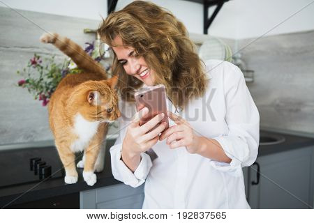 Woman in a white man's shirt is standing in the kitchen. A girl shows the cat a smartphone screen and smiles. Cat is looking at the phone. stock photo