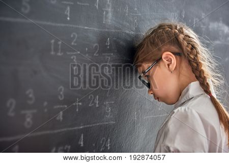 Tough day at school! Sad child near the blackboard indoors. Kid is learning in class. Complex math,