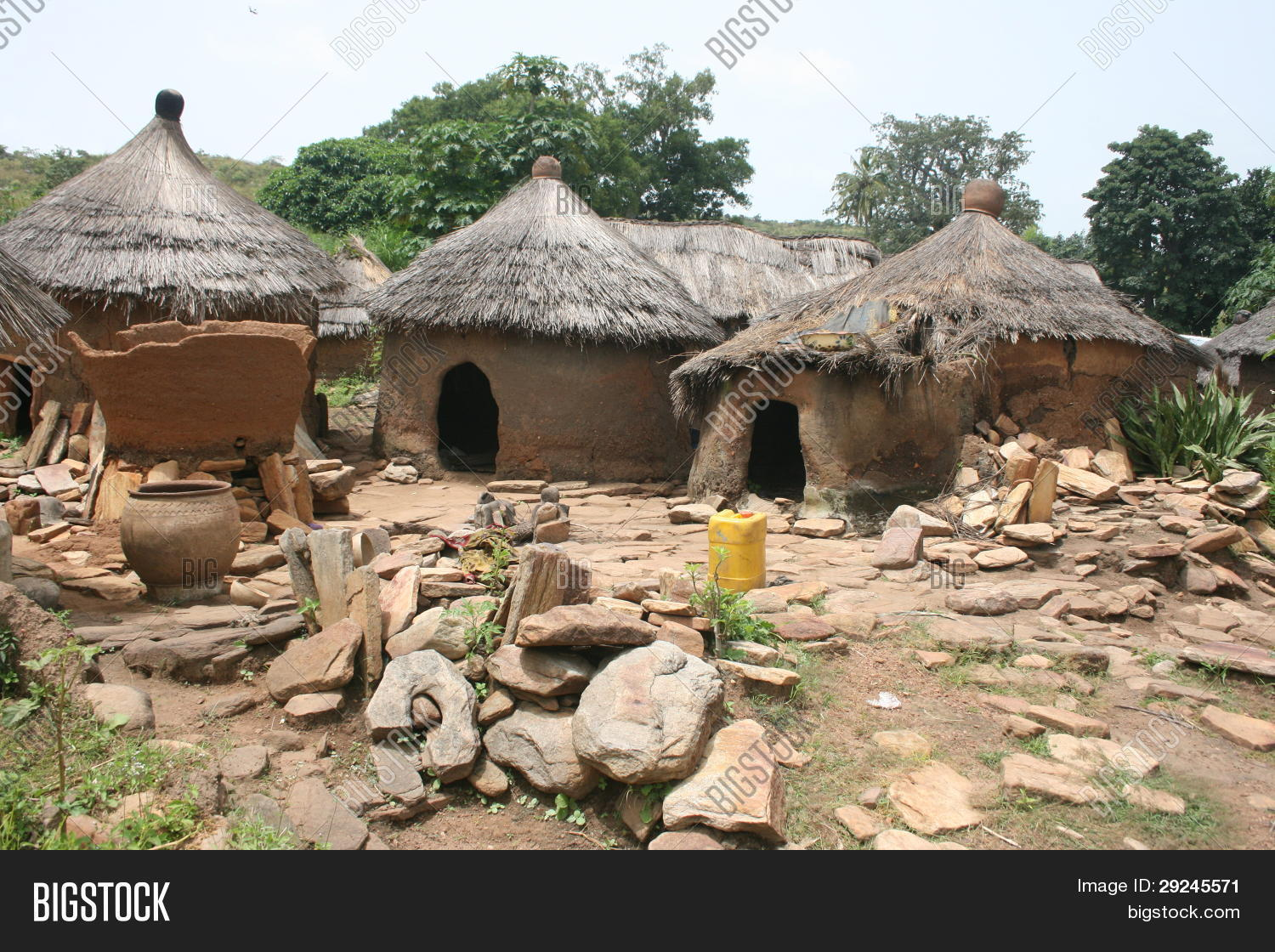 Tupical West African Village Of Mud And Dung Huts With Thatched
