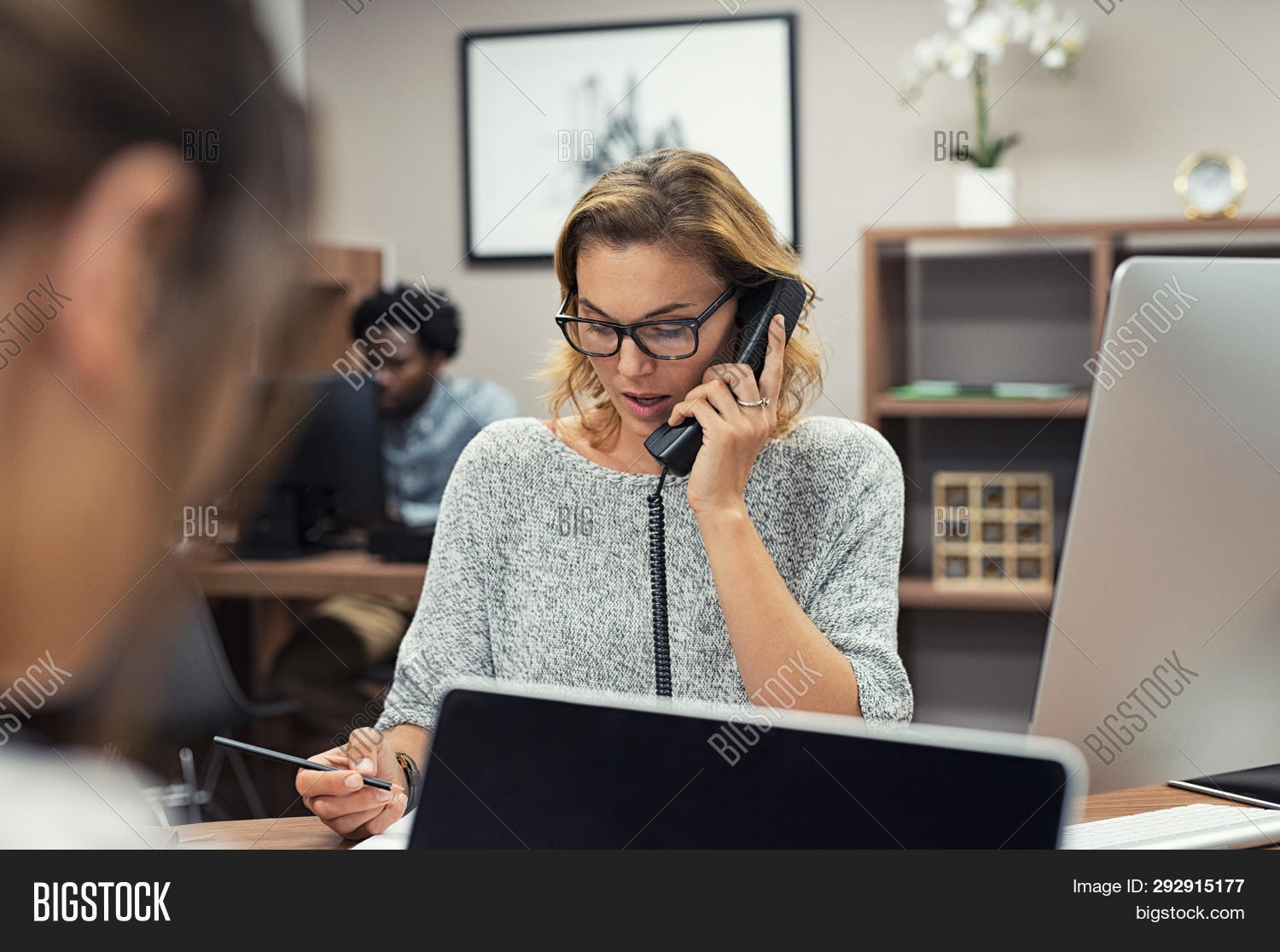 Mature businesswoman talking on phone in office. Casual business woman talking on landline phone in