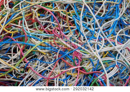 Flexible electrical wire is very much confusing. Cables of different colors. Confusion, chaos, disorder. A tangle of twisted wires. Lots of tangled cables. Background or backdrop. stock photo