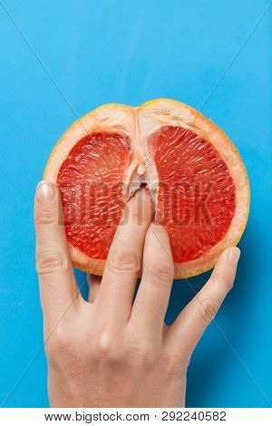 Two female fingers in grapefruit, woman masturbation and sex concept. Vagina and clitoris symbol. stock photo