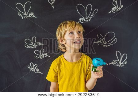 The boy is bitten by mosquitoes holding a fumigator on a dark background. On the blackboard with chalk painted mosquitoes stock photo
