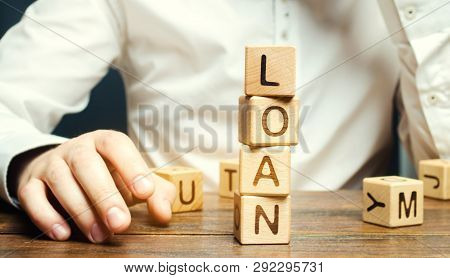 Wooden blocks with the word loan and businessman. Consumer, banking and property loan. Business and entrepreneurial development. Small business loans. Interest rate repayment. Planning stock photo