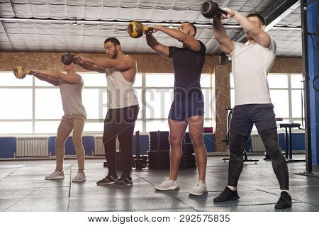 Male Focused Friends Lifting Kettlebells During Workout Session in Gym. High Intense Exercise Class in Gym. Teamwork, Sports and Fitness Concept. stock photo