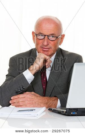 A successful older businessman sits in his office with a laptop. stock photo